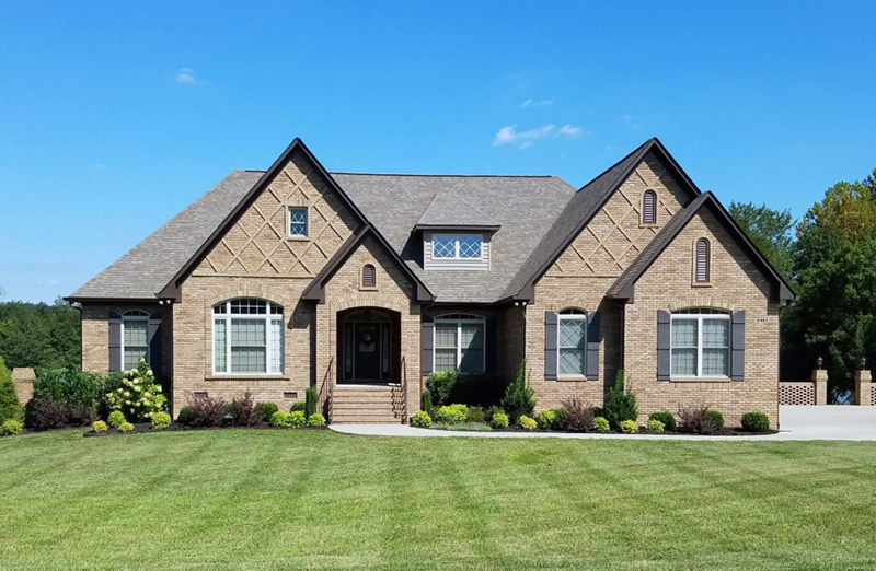 Stone Covered Two-Story Home Has Country Style And Looks Like A One-Story Style
