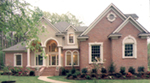 Two-Story Stucco Home With Arched Windows And Entry