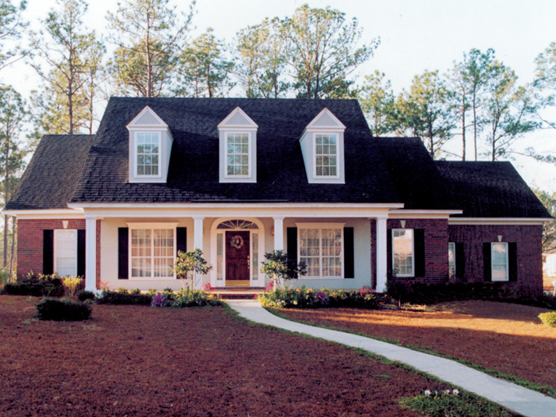 Brick Home With Sweeping Front Covered Porch And Triple Dormers