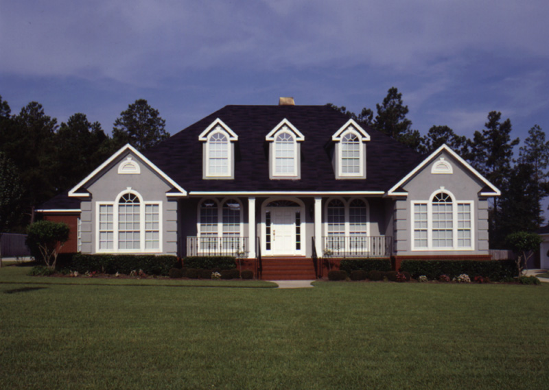 Symmetrical Home With Stately Front Porch And Windows