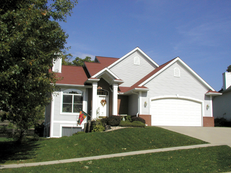 traditional style home with two levels and a pillared front porch - Multi Level Home Plans