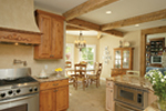 A rustic stone floor, wood ceiling beams and honey-stained cabinetry create a kitchen with great country style perfect for casual family meals and food preparation.