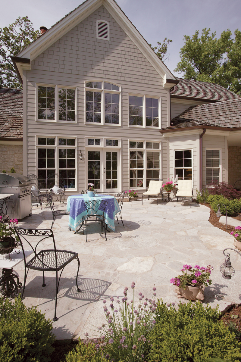 the oversized rear patio enjoys a striking backdrop of the great room's massive window wall. With plenty of space for dining, relaxing or entertaining, this outdoor getaway is a convenient escape.