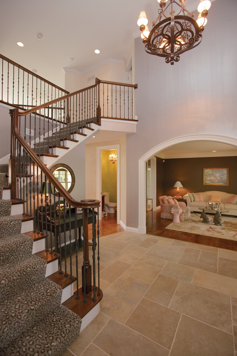 The intricate double staircase can be accessed in both the foyer and kitchen and leads to the second floor living spaces while highlighting the two-story ceiling and decorative nooks.