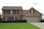 Traditional Two-Story Home With Brick Exterior And Front Loading Garage