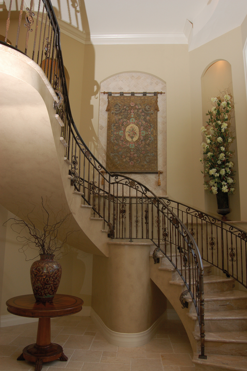The stunning two-story foyer has a circular staricase adorned with a mediterranean style wrought-iron railing. As the staircase ascends to the second floor it offers an artistic Old World feel to the interior.